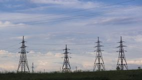 Power lines and sky with clouds. High voltage power lines.Field and aerial lines, silhouettes at dusk.Electric power industry and nature concept.Field and stock photography
