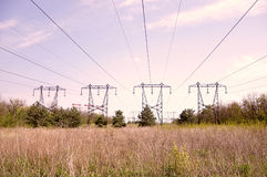 High-voltage power lines in field Stock Photography