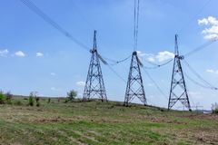 High-voltage power lines in green field against blue sky Royalty Free Stock Photo