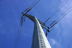 High Voltage Power Lines intersect at a large metal Utility pole. In Maine against a blue sky Stock Photography