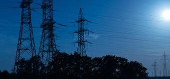 High-voltage power lines in the light of the rays of the setting sun, transporting electricity over long distances. royalty free stock photography