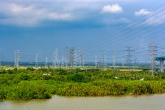 High-voltage power lines over jungle. High-voltage power lines crosses jungle and river stock photography