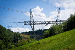 High voltage power lines over the mountains. In the forest Royalty Free Stock Photography