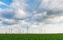 High-voltage power lines passing through a green field, on the background of a beautiful cloudy sky royalty free stock photography