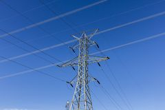 High-voltage power lines and pylon against blue sky II Stock Photo