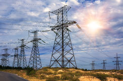 High-voltage power lines and stormy sky with the sun Stock Photo
