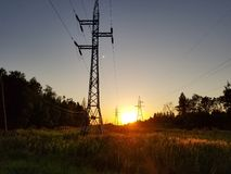 High-voltage power lines during summer sunset royalty free stock photo