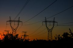 high-voltage power lines at sunset. electricity distribution sta royalty free stock image