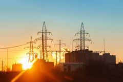 High-voltage power lines at sunset. Electricity distribution station royalty free stock image