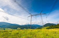 High voltage power lines tower in Carpathian mount. Ains. lovely green energy industry concept. beautiful landscape in autumn with blue sky and some clouds Royalty Free Stock Images