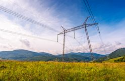 High voltage power lines tower in Carpathian mount. Ains. lovely green energy industry concept. beautiful landscape in autumn with blue sky and some clouds Royalty Free Stock Photos