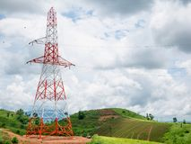 High voltage power lines tower on green mountain. And sky with clouds Royalty Free Stock Image