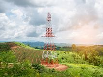 High voltage power lines tower on green mountain Stock Photos