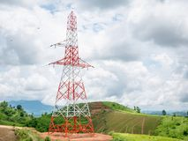High voltage power lines tower on green mountain. And sky with clouds Royalty Free Stock Photos