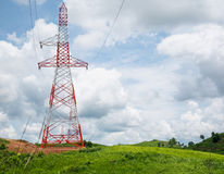 High voltage power lines tower on green mountain Stock Photo