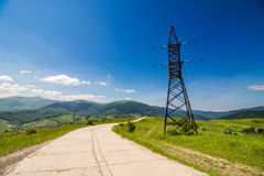 High voltage power lines tower in mountains. High voltage electric power lines tower near the road in mountains stock images
