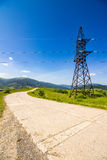High voltage power lines tower in mountains Stock Image