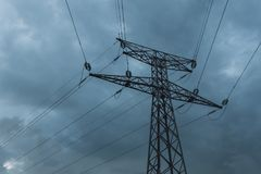 High voltage power lines and transmission towers on a cloudy day. Poles and overhead lines silhouettes in the dusk Stock Images