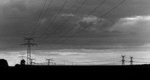 High voltage power lines and transmission towers at sunset. Poles and overhead lines silhouettes. Electricity generation Stock Photography