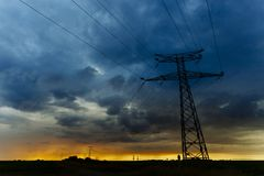 High voltage power lines and transmission towers at sunset. Poles and overhead power lines silhouettes in the dusk Stock Photo