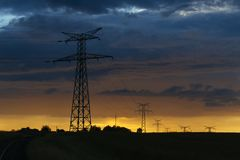 High voltage power lines and transmission towers at sunset. Poles and overhead power lines silhouettes in the dusk Stock Images
