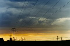 High voltage power lines and transmission towers at sunset. Poles and overhead power lines silhouettes in the dusk Royalty Free Stock Photography