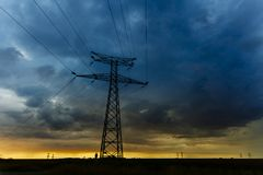 High voltage power lines and transmission towers at sunset. Poles and overhead power lines silhouettes in the dusk Stock Photos