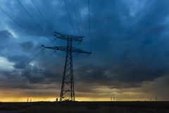 High voltage power lines and transmission towers at sunset. Poles and overhead power lines silhouettes in the dusk Stock Photography