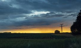 High voltage power lines and transmission towers at sunset. Poles and overhead power lines silhouettes in the dusk Royalty Free Stock Photos