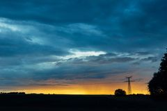 High voltage power lines and transmission towers at sunset. Poles and overhead power lines silhouettes in the dusk Royalty Free Stock Images