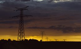 High voltage power lines and transmission towers at sunset. Poles and overhead power lines silhouettes in the dusk Stock Image