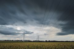 High voltage power lines, transmission towers and wind turbines in agricultural fields on a cloudy day. Poles and Royalty Free Stock Photo