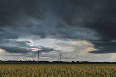 High voltage power lines, transmission towers and wind turbines in agricultural fields on a cloudy day. Poles and Stock Photography