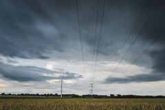 High voltage power lines, transmission towers and wind turbines in agricultural fields on a cloudy day. Poles and Stock Images