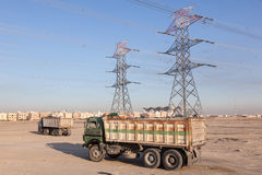 High voltage power lines and trucks. In Kuwait, Middle East Royalty Free Stock Photos