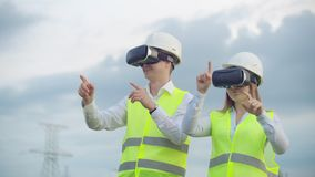 High-voltage power lines under the control of two engineers using virtual reality to control power. Alternative energy. Sources in a modern city stock video footage