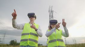 High-voltage power lines under the control of two engineers using virtual reality to control power. Alternative energy. Sources in a modern city stock video