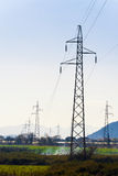 High-voltage power lines in the valley stretching into dista Stock Images