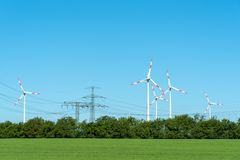 High voltage power lines and wind turbines stock photos
