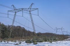 High-voltage power lines in winter time. High voltage electric transmission tower energy pylon. High-voltage power lines in winter time at snowy forest. High royalty free stock images