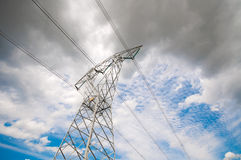 High voltage power pole over a cloudy sky Stock Image