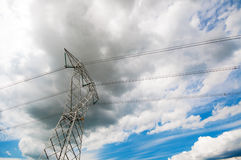 High voltage power pole over a dark gray sky Stock Images