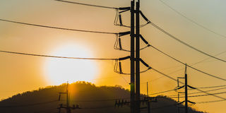 High voltage power poles and lines silhouette royalty free stock photos