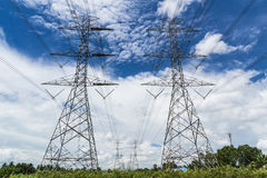 High voltage power pylon against blue sky Stock Photo