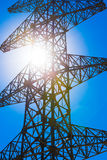 High voltage power pylon and sun Royalty Free Stock Images