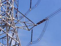 High voltage power pylons against blue sky Royalty Free Stock Image