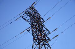 High voltage power pylons against blue sky and sun rays Royalty Free Stock Photos