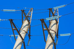 High voltage power pylons against blue sky Stock Images