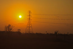 High voltage power pylons in sunset Stock Photo