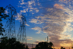High voltage power pylons in sunset scene twilight stock photo